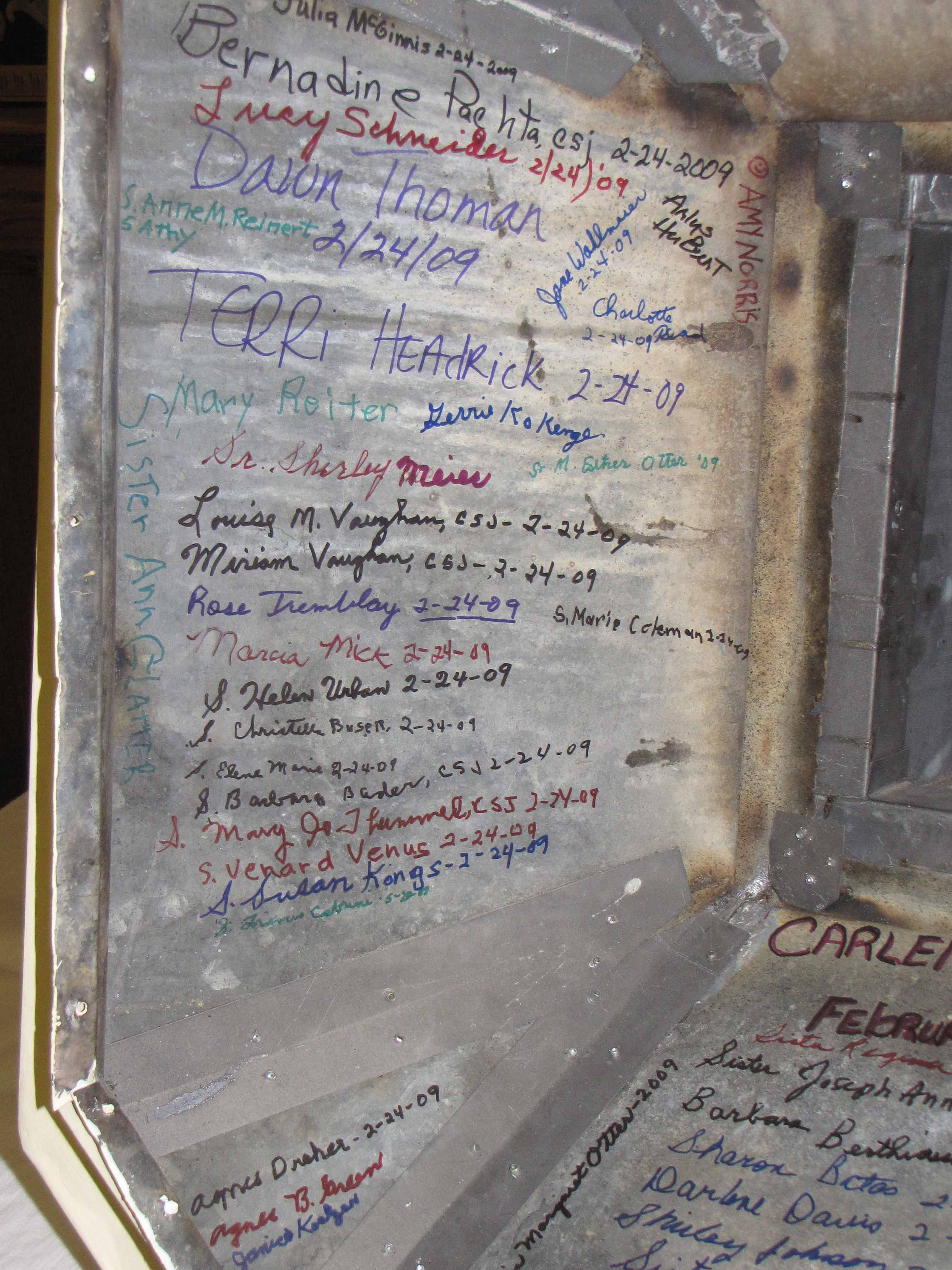 The inside surface of the cross base is crowded with signatures.