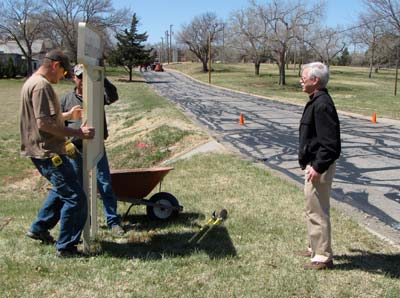 Facilities manager Greg Gallagher watches as grounds supervisor Bob Kearn and Eric McDaniel ensure the sign is level.