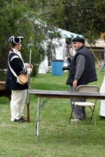 Meanwhile, a Revolutionary War era re-enactor chats with a photographer.