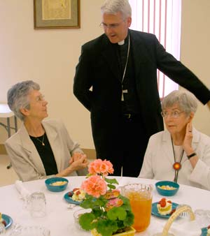 Bishop Paul Coakley chats with Sister Judy Stephens, left, and Sister Lucy Schneider at the dinner on May 13.
