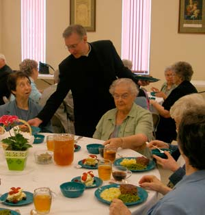 Father Randall Weber serves Sister Margaret Rourke, left, as Sister Mary Reiter and other Sisters of St. Joseph enjoy their meal May 13.