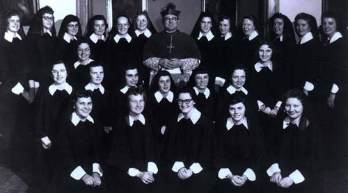The women who were received into the Sisters of St. Joseph of Concordia in 1959 gathered for a group photo with Bishop Fredrick Freking at the Motherhouse. Sisters who are deceased are noted with an asterisk (*); women who left the order are noted with a pound sign (˚). All left to right, BACK ROW: Marilyn Yantz#, Elaine Meyer#, Veronica Roy*, Donna Otter, Mary Margaret Miller#, Betty Suther, Bishop Freking, May Lou Stromitis#, Marcia Allen, Madonna Readey*, Mary Jo Thummel, Mary Lou DeMay#, Diane Brin. MIDDLE ROW: Bernardine Divel*, Faye Huelsmann, Jean Befort, Philomene Reiland, Rosemary Farrell, Virginia Pearl, Polegia Bloomenradar#, Shirley Meier. FRONT ROW: Bernita Heier#, Anna Marie Broxterman, Nancy Meade, Patricia McLennon, Marilyn Stahl. Of these 25, three have died, seven left the order and 15 remain as active Sisters of St. Joseph.