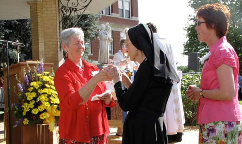 Sister Faye Huelsmann offers the wine to Sister Gilberta Appelhans as Sister Christy Cogil waits behind her.