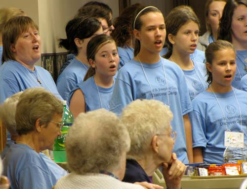 The Discover Camp girls sing for the sisters in the dining room.