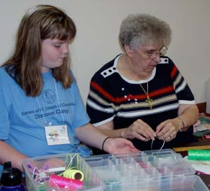 Sister Mary Jo Thummel teaches one of the girls beading during an afternoon crafts session.