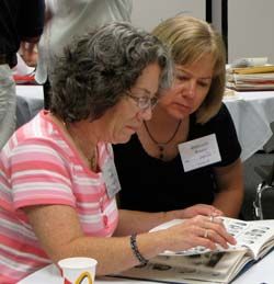 Two members of the Class of 81, Mary Moriarity Madrid of Loveland, Colo., left, and Deborah Silhan Britain of Lenexa, Kan., review their yearbook at the Marymount College All-School Reunion Saturday morning.