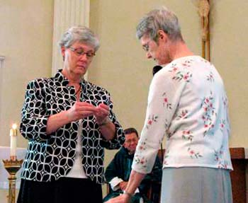 New Sister Rosemary Foreman, left, accepts the ring signifying her entrance into the congregation from Sister Marcia Allen.