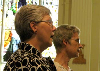 Rosemary Foreman, left, sings as she waits for her profession of her vow during Mass Sunday. Beside her is Sister Marcia Allen, president of the congregation.
