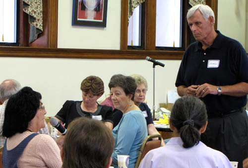 Joel Wright, who chairs the Salina Regional Transit Breakthrough Team, listens as Judie Deal, seated at left, explains some of Concordia's public transportation limitations during Thursday's working lunch at the Sisters of St. Joseph Motherhouse.