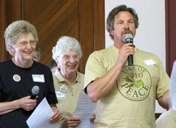 Cloud County Community College music instructor Patrick Sieben, who has written two songs for the Concordia Year of Peace, encourages the audience to sing during Thursday's working lunch by telling them, 'If you can read music, sing loud. If you can't read music, sing louder,' to the delight of Sisters Betty Suther, left, and Carolyn Teter.