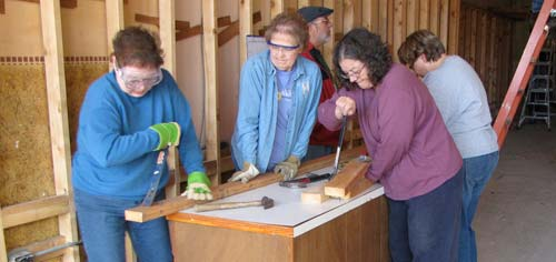 One goal was to salvage as much of the lumber as possible, and that meant removing nails — a task taken on by, from left, Penny Larsen, Pam Campbell, Joyce Swenson and Christy Hasch.