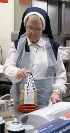 Sister Edwardine Flavin weighs each package of Heavenly Bits to ensure consistency.