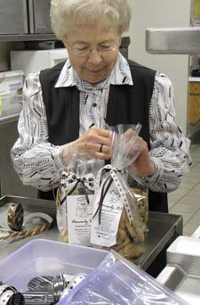 Sister Francis Margaret Otter decorates bags of biscuits with dog-themed ribbons.