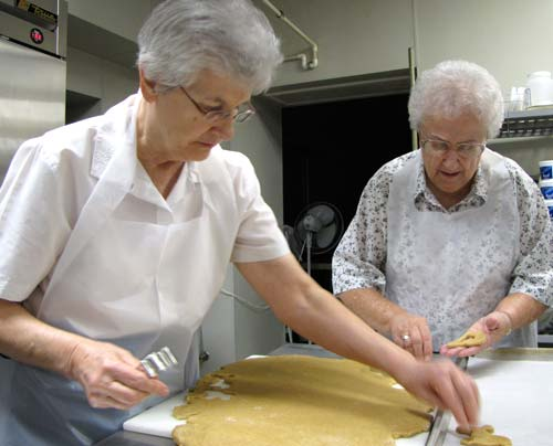 Sisters Janis Wagner, left, and Christella Buser cut dog biscuit shapes from the peanut butter dough as part of the process in making Heavenly Bits.