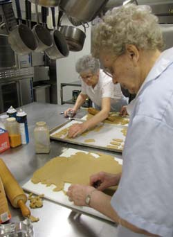 Sisters Janis Wagner, left, and Geraldine Kokenge prepare the peanut butter dough to be cut into dog biscuits.