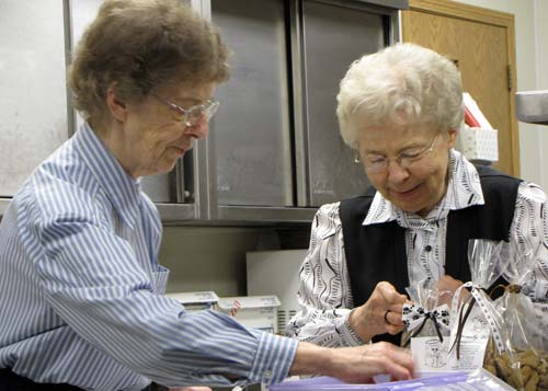 Sisters (and sisters) Mary Esther Otter, left, and Francis Margaret Otter package the finished biscuits for sale.