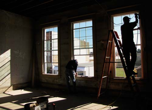 Curtis Mansfield, left, and Gene Ganstrom, both employees of the Sisters of St. Joseph of Concordia, work Thursday to finish installing new windows in the second floor of what will be the new Neighbor to Neighbor center in downtown Concordia.  The upper floor in the 121-year-old building had only been used for storage in recent years, and the windows had been boarded up for decades.