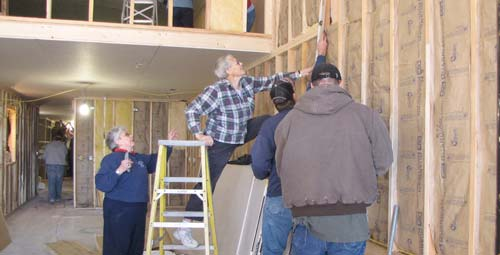 Sister Cecelia Green, on ladder, measures for insulation while Sister Ramona Medina gets ready to cut.
