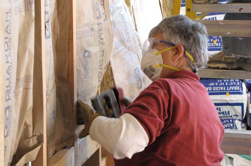 Sister Esther Pineda helped organize the volunteer effort at the new Neighbor to Neighbor center, and then joined the workers in putting in insulation throughout the East Sixth Street building.
