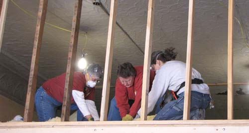 Sister Esther Pineda, from left, Sister Jean Befort and Janie Stein get ready to begin insulating the newly reframed second floor of the 122-year-old building.