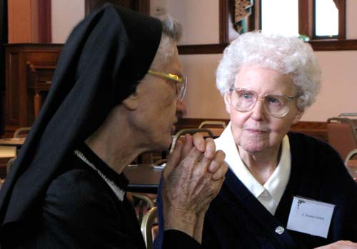 Sisters Gilberta Appelhans, left, and Norma Schlick take time for a quiet conversation as they sample of open house treats.