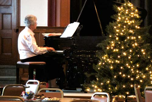 Sister Janis Wagner entertains with holiday piano favorites during Sundays open house.