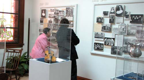 Sister Marie Coleman, left, explains the history boards in one of the Motherhouses Heritage Rooms to a visitor Sunday afternoon.