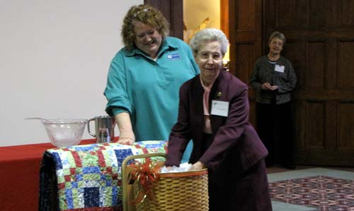 Sister Jane Guenette draws the winning entry for a donated quilt as Martha Bryant, executive director of development for the Sisters of St. Joseph, looks on.