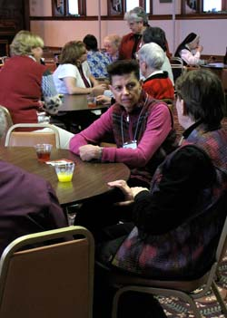Sue Sutton, in pink, and Sister Jean Rosemarynoski, at right, are two of the women taking part in a lively table conversation during Sundays open house.