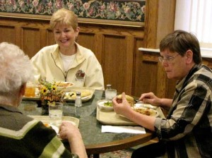 The two newest professed agrégées, Sister Sharon Hayes, center, and Jan McCormick, right chat with Sister Agnes Bernita Green over dinner Saturday.