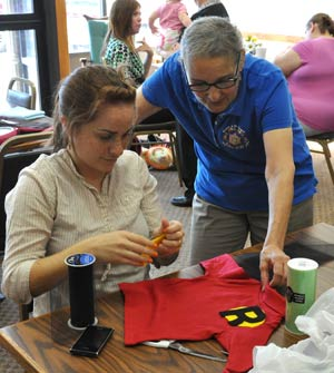 Brodie looks on as a young mother creates Halloween costumes for her children at Neighbor to Neighbor, a ministry of the Sisters of St. Joseph.