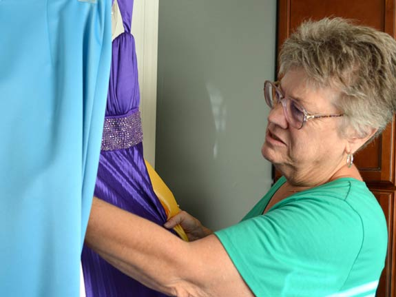 Sister Beth Weddle looks through some of the colorful prom dresses that have already been donated.