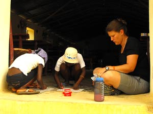 Sister Julie Christensen colors with two of the Haitian girls.