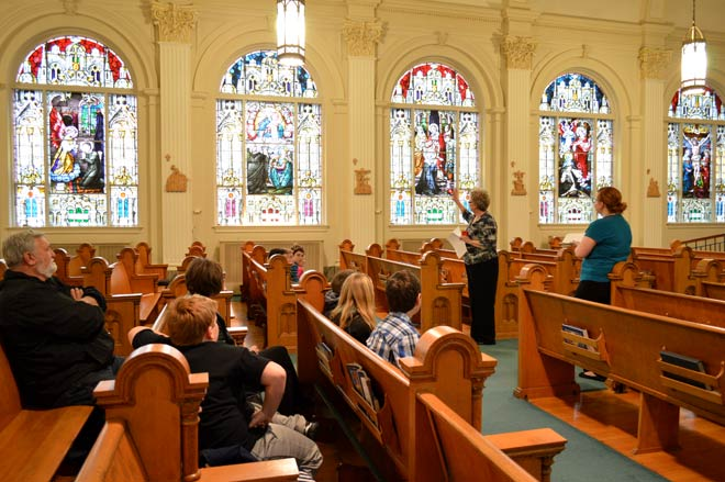 As part of Monday's tour, Jane Wahlmeier explains how the stained-glass windows in the Motherhouse chapel were created in Chicago and then brought to Concordia by train in 1907.