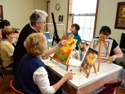 Sister Ramona Medina, standing, offers guidance during one of her twice-weekly painting classes at Neighbor to Neighbor.