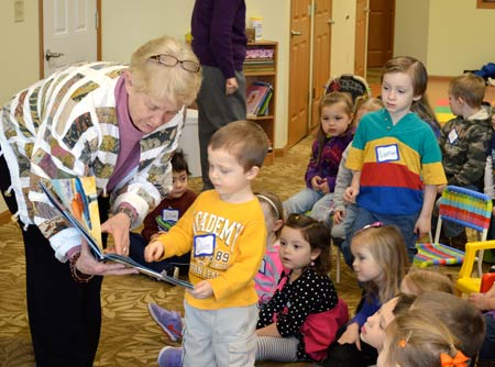 """Carol Ruud gets out among her preschool audience during a """"Reading with Friends"""" storytime at Neighbor to Neighbor in February 2013."""