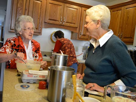 Betty Miller, left, chats with Sister Pat McLennon during a baking class offered each week by volunteer Theresa Peltier, who is working in the background.
