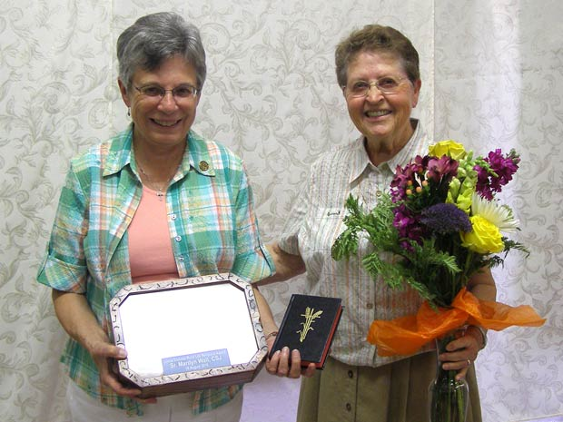 After the ceremony Aug. 16 in Bird City, Kan., Sister Marilyn Wall of Washington, left, poses with the new Catholic Rural Life Service Award presented to her by Sister Carm Thibault, right, a member of the Salina Catholic Rural Life Commission.