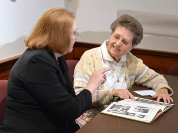 Sister Carm Thibault, right, shows Jeanne Goodman the picture of her sister Martha Wessling Bieber in the 1971 Marymount College yearbook.