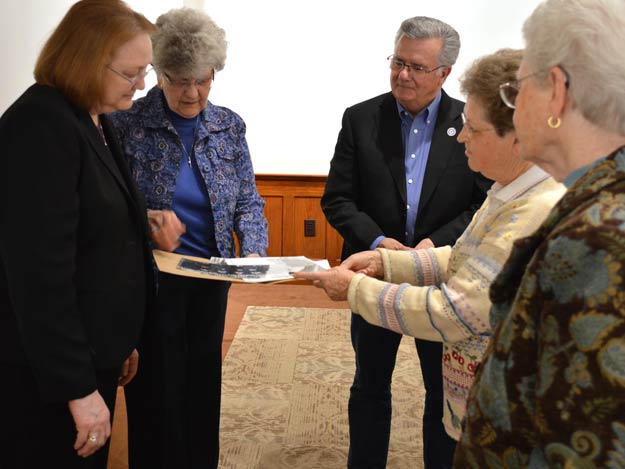 Looking through old photographs as part of the Heritage Center tour on Thursday, Feb. 18, were, from left, Jeanne Wessling Goodman, Sister Bernadine Pachta, Jeff Bieber, Sister Carm Thibault and Sister Pat McLennon.