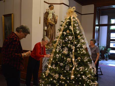 Throughout their time in Concordia, the novices pitched in to help with projects — including decorating for Christmas at the Motherhouse. Here Sister Mary Anne Larocque, center, works with volunteer Connie Palacio, left, and Sister Jean Befort on the tree in the main foyer.