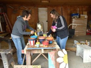 Development Director Holly Brown, left, and assistant Ambria Gilliland take over a Motherhouse garage to hand-paint flower pots and garden signs for the May 7 sale.