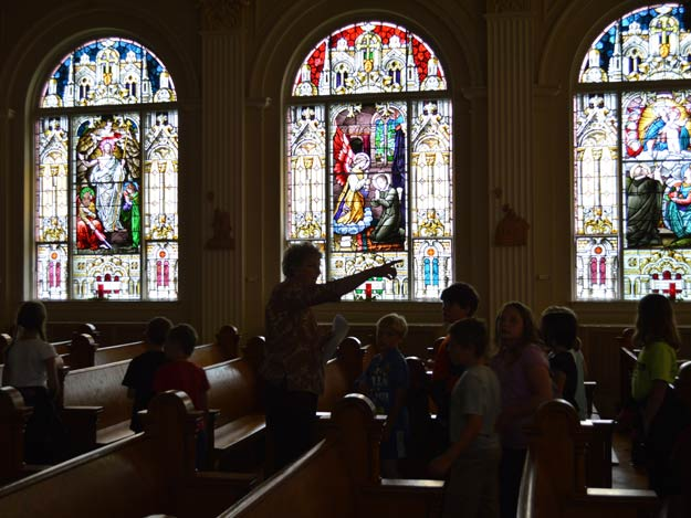 Sister Betty Suther is silhouetted against one of the 109-year-old stained glass windows in the Motherhsouse chapel.
