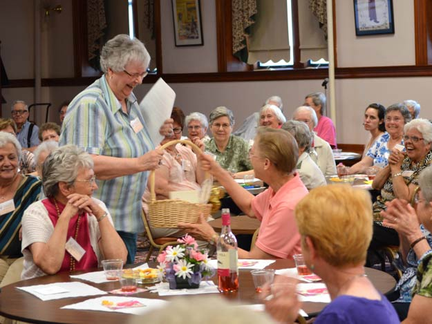 Sister Mary Lou Roberts, standing, presents a basket of cards and gifts to outgoing Leadership Council member Sister Therese Blecha.