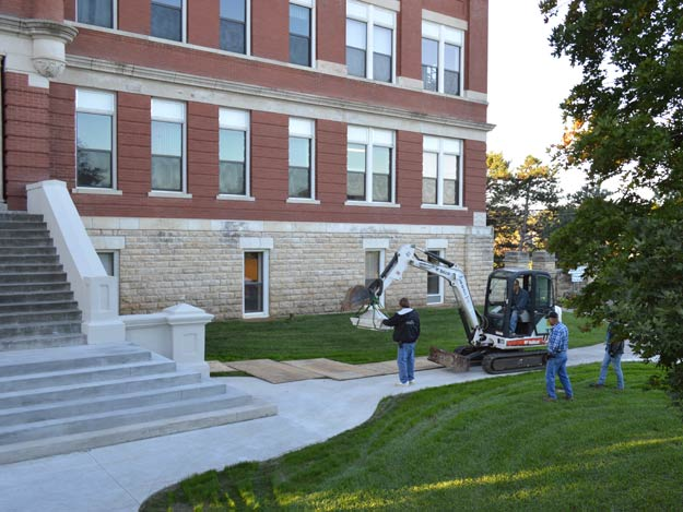 Workers use a Bobcat loader to carry one of the 1,300-pund capstones to the Motherhouse staircase this morning.