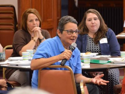 """Sister Christina Brodie says many of the families in the Hands Across Our Community program do not fit the """"obvious poor"""" stereotype. Seated behind her are Susan LeDuc, left, and Tonya Merrill, right."""